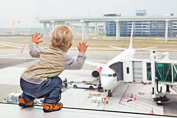 Baby boy in airport transit hall looking at airplane stock photo