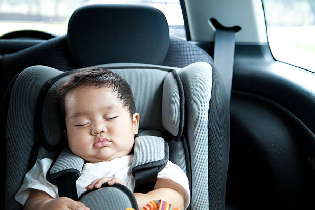 petit garçon dans un siège de voiture - child car sleep photos et images de collection