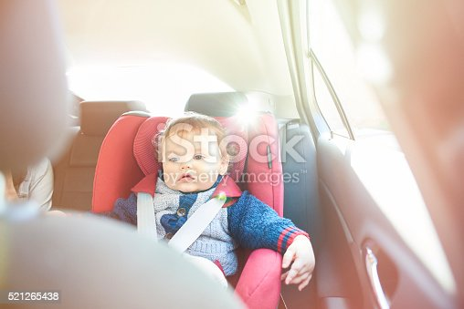 istock Baby boy in car seat watching DVD 521265438