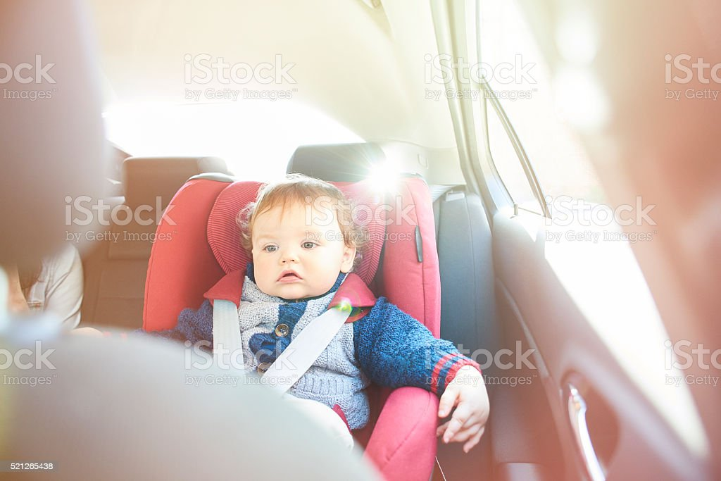 Baby boy in car seat watching DVD stock photo