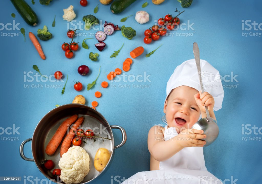 Baby boy in chef hat with cooking pan and vegetables stock photo