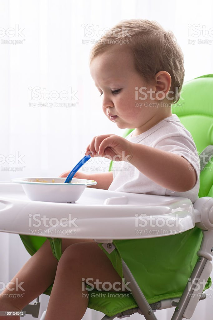 Baby boy sitting in his dining chair with a spoon in his hand