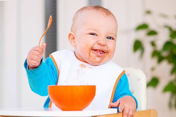 Babyjunge im Hochstuhl Fütterung selbst – Foto