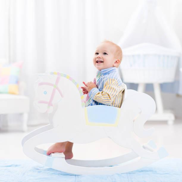 baby boy in rocking horse toy - pferde schlafzimmer stock-fotos und bilder