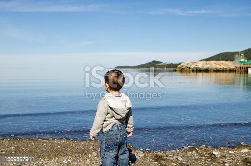 Baby boy in shore of St. Lawrence river during summer day in Gaspesie (Les Mechins)