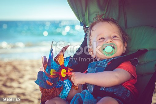 Cute baby sitting in stroller on the beach in summer
