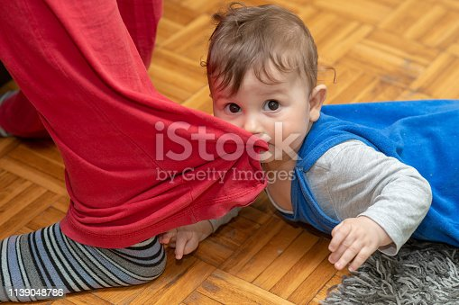 Baby boy is biting mom's trouser leg