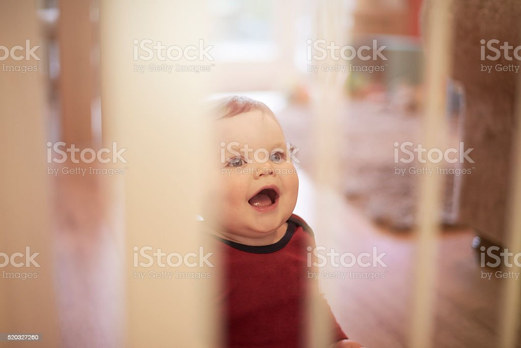 Baby boy laughing behind baby safety gate stock photo