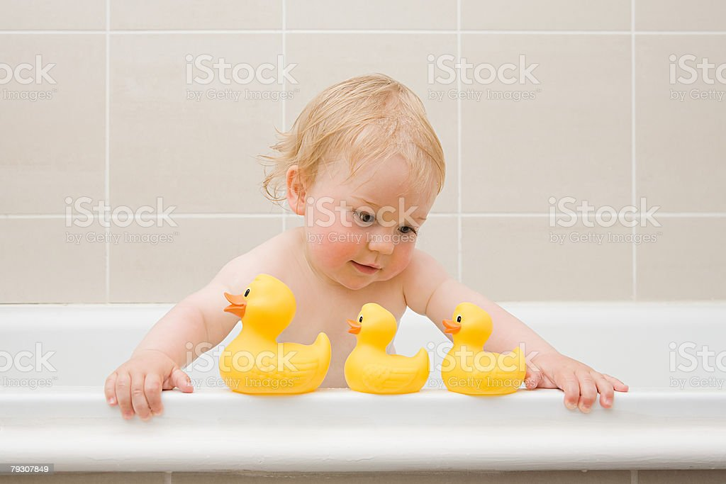 A baby boy looking at a row of rubber ducks stock photo