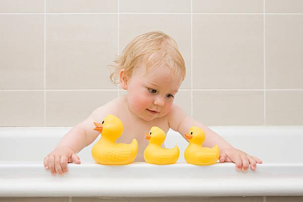 a baby boy looking at a row of rubber ducks - baby bathtub bildbanksfoton och bilder