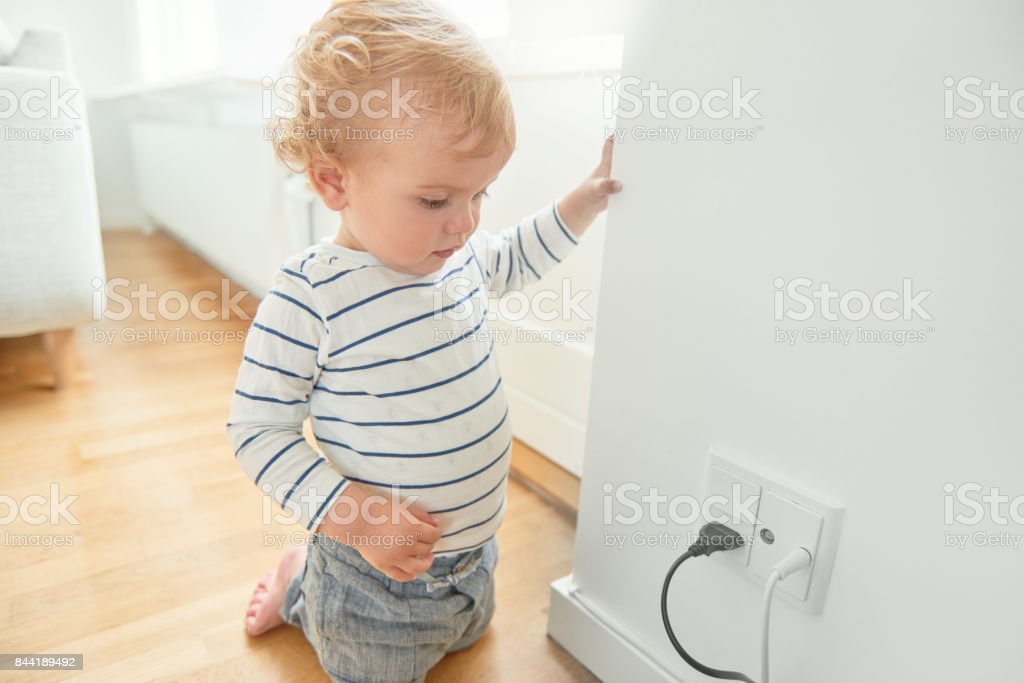 Baby boy looking at electrical plug in the wall. stock photo