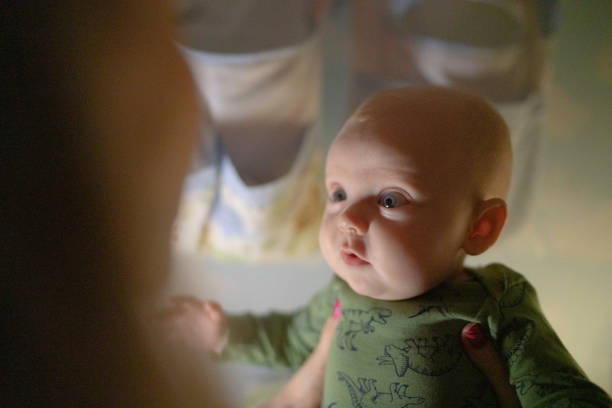 baby junge schaut auf seine mutter - anzieh nacht stock-fotos und bilder