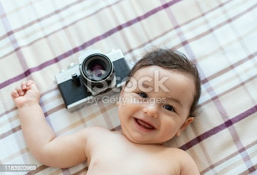 Baby boy lying on bed with SLR Camera
