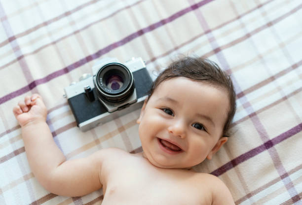 Baby boy lying on bed with SLR Camera stock photo