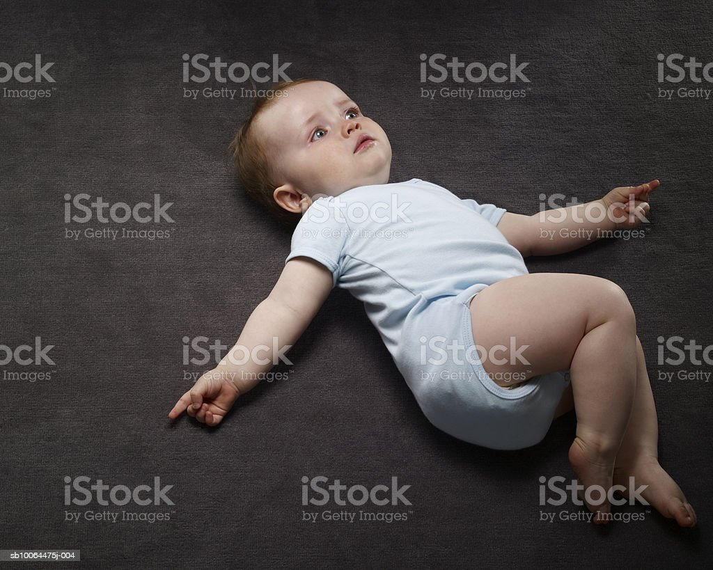 Baby boy (9-12 months) lying on floor, elevated view 免版稅 stock photo