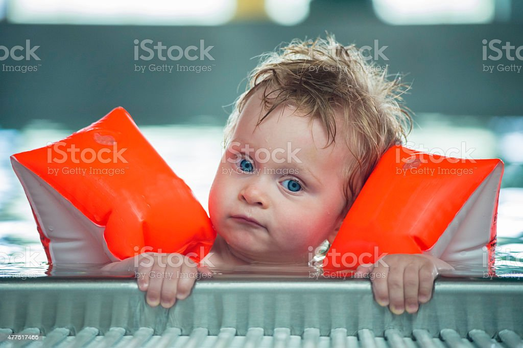 Baby boy makes face in a swiming pool stock photo