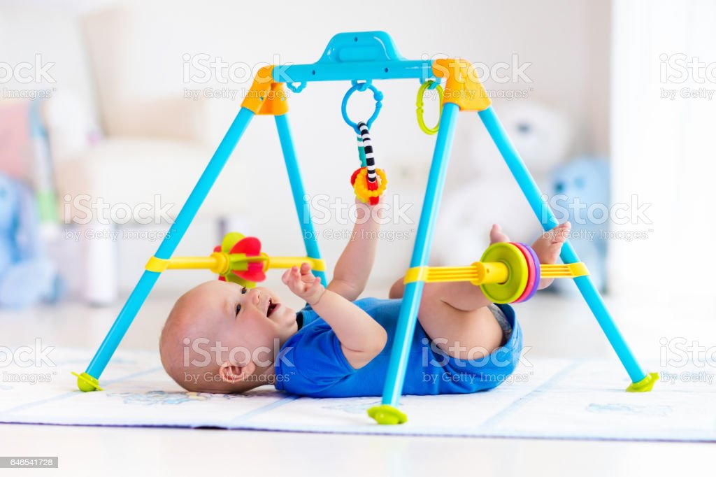 Baby boy on play mat. Child playing in gym. stock photo