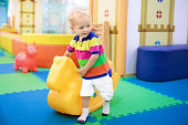 Child playing with hopping horse. Indoor activity toys for kids. Kindergarten or preschool play room. Toddler kid at day care playground. Swing pony for children. Baby boy with toy at daycare.