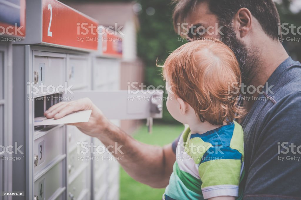 Baby Boy Opening a Mailbox with Parent stock photo