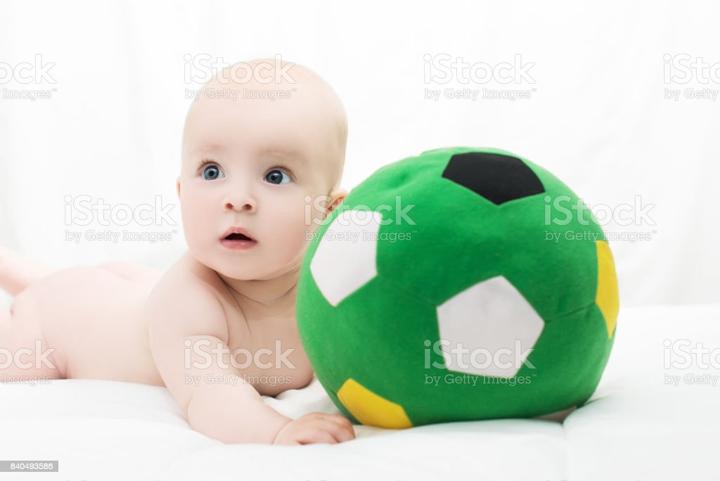 baby boy or girl lying down on his belly and playing with soccer ball stock photo