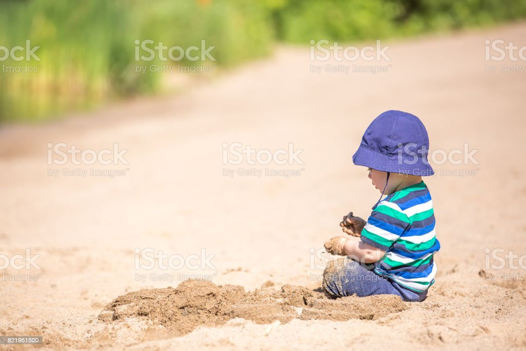 Baby Boy Playing in Sand at Beach stock photo