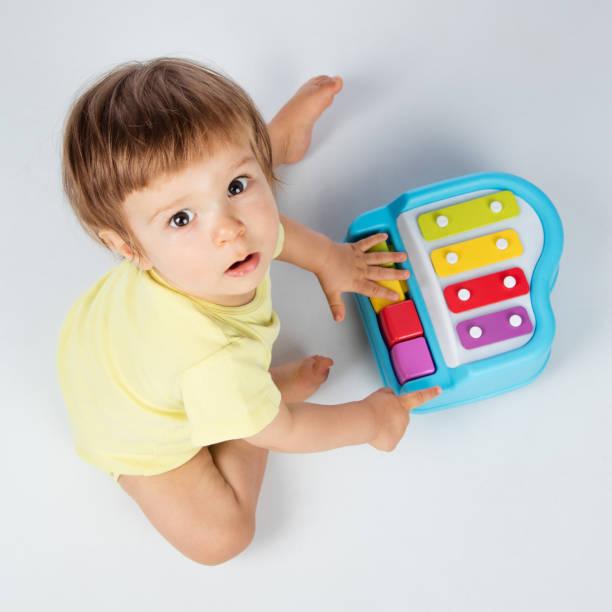 baby boy spielt spielzeug klavier - lautbildungsspiele stock-fotos und bilder