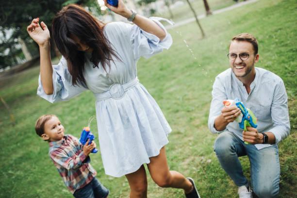 Baby Boy spielen Wasserpistolen mit jungen Eltern im park – Foto
