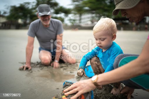 Baby boy playing whit bucket and shovel at the beach with his grandfather