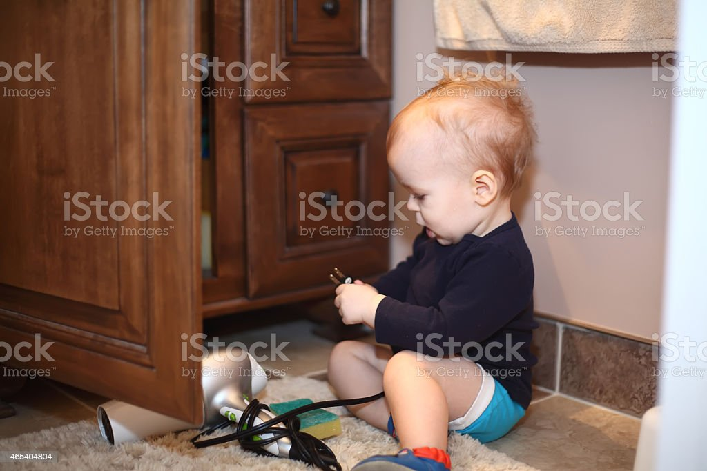 Baby boy playing with a blowdryer in a bathroom stock photo