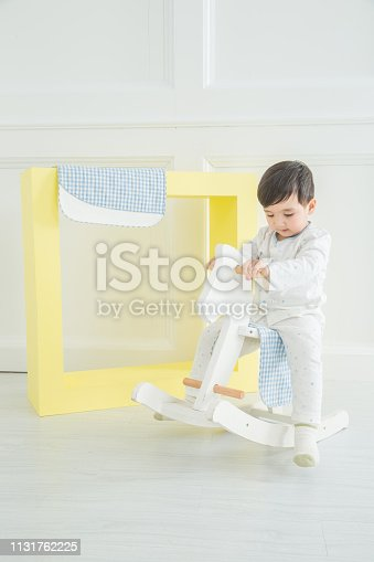 112301234 istock photo Baby boy playing with a rocking horse on grey background 1131762225
