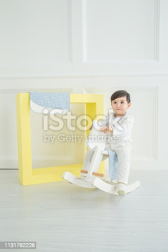 112301234 istock photo Baby boy playing with a rocking horse on grey background 1131762226