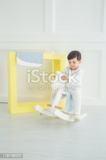 112301234 istock photo Baby boy playing with a rocking horse on grey background 1131762227