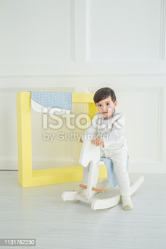 112301234 istock photo Baby boy playing with a rocking horse on grey background 1131762230