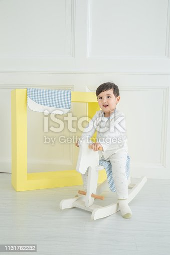112301234 istock photo Baby boy playing with a rocking horse on grey background 1131762232