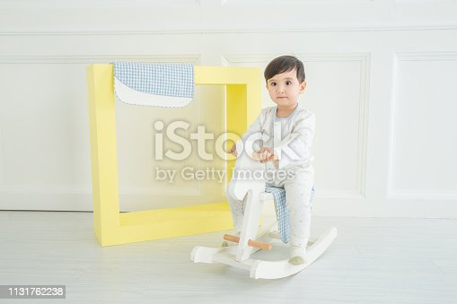 112301234 istock photo Baby boy playing with a rocking horse on grey background 1131762238