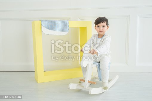 112301234 istock photo Baby boy playing with a rocking horse on grey background 1131762240