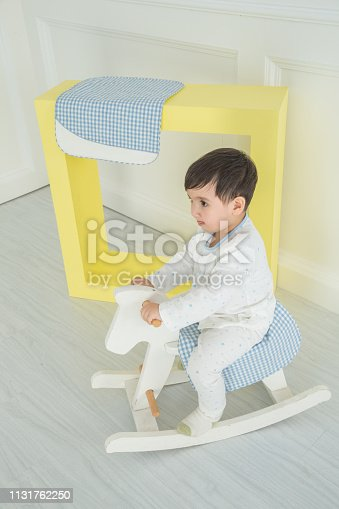 112301234 istock photo Baby boy playing with a rocking horse on grey background 1131762250