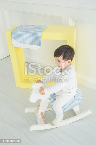 112301234 istock photo Baby boy playing with a rocking horse on grey background 1131762256