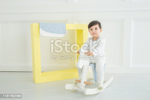 112301234 istock photo Baby boy playing with a rocking horse on grey background 1131762258