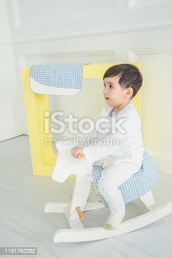 112301234 istock photo Baby boy playing with a rocking horse on grey background 1131762262