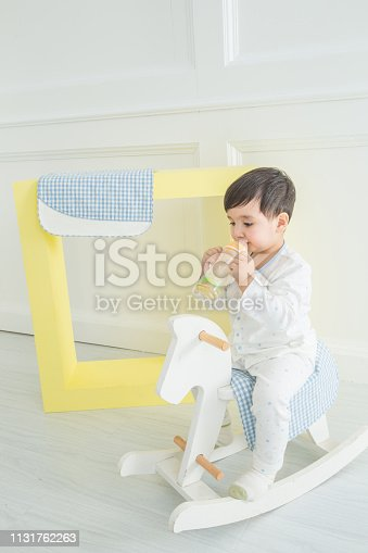 112301234 istock photo Baby boy playing with a rocking horse on grey background 1131762263