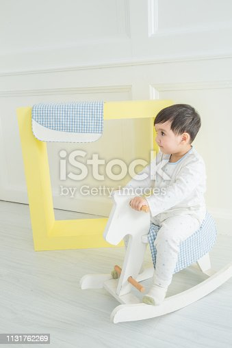 112301234 istock photo Baby boy playing with a rocking horse on grey background 1131762269