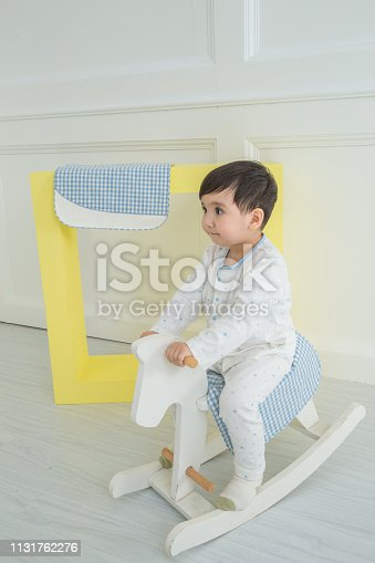 112301234 istock photo Baby boy playing with a rocking horse on grey background 1131762276