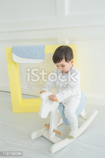 112301234 istock photo Baby boy playing with a rocking horse on grey background 1131762280