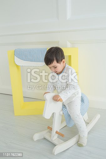 112301234 istock photo Baby boy playing with a rocking horse on grey background 1131762285