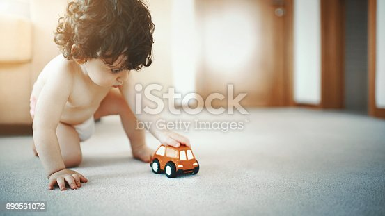 Closeup of a two year old toddler with curly brown hair sitting on the living room floor and playing with an orange toy car.He's wearing diapers only.