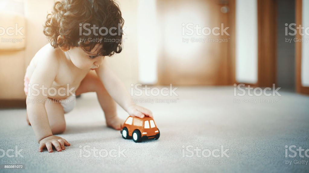 Baby boy playing with a toy car. stock photo