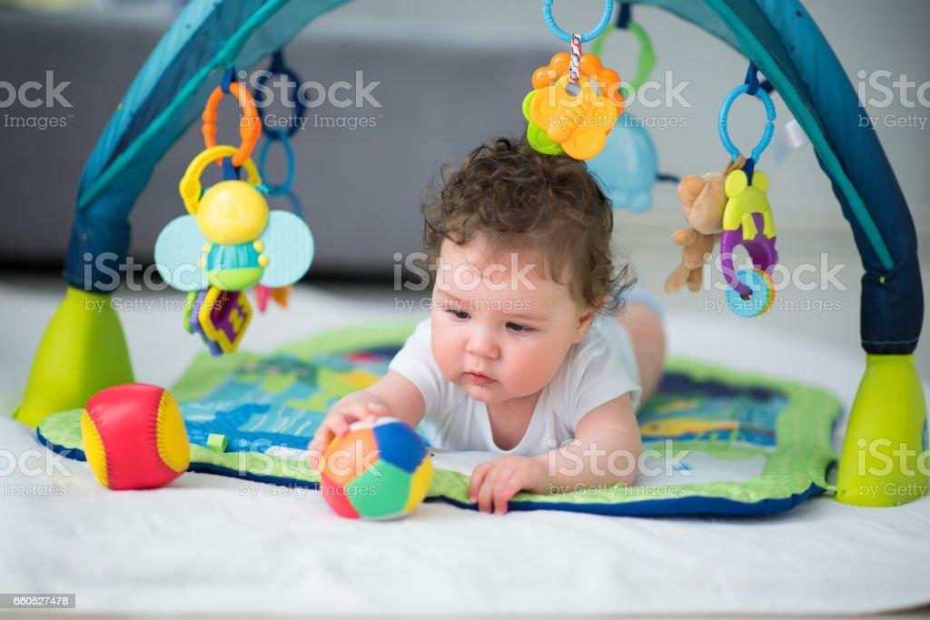 Beautiful baby boy playing with baseball ball inside baby playroom,...