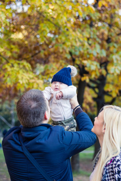 Baby boy playing with his mom and dad in the park stock photo