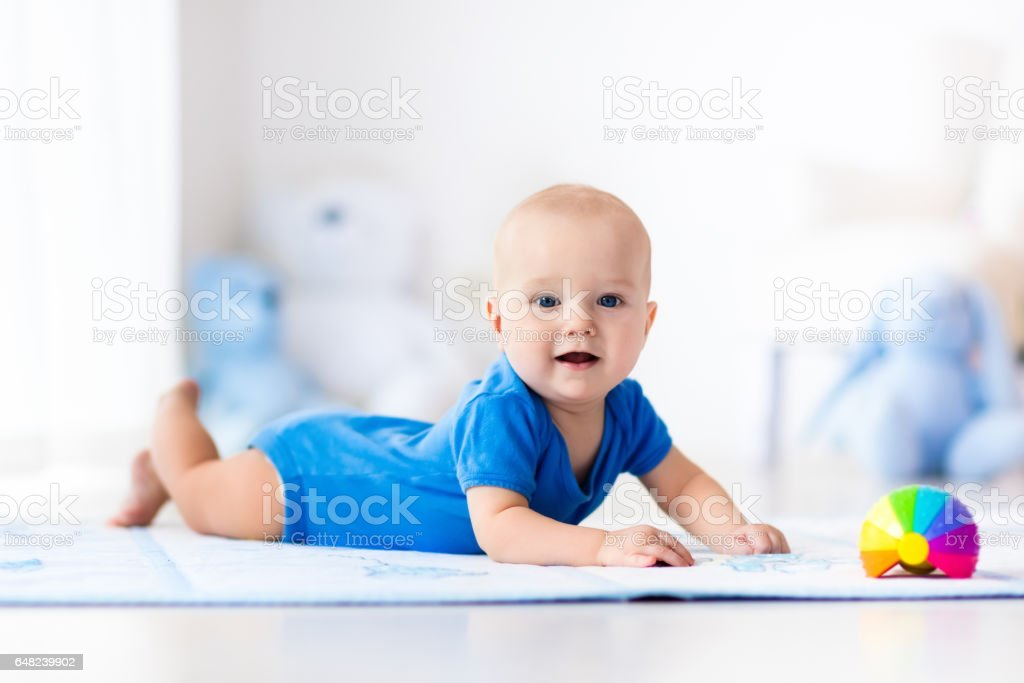 Baby boy playing with toy ball stock photo